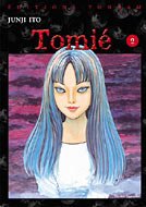 A coloured manga cover depicting a typical Tomie pose.  Demure and threatening underneath.